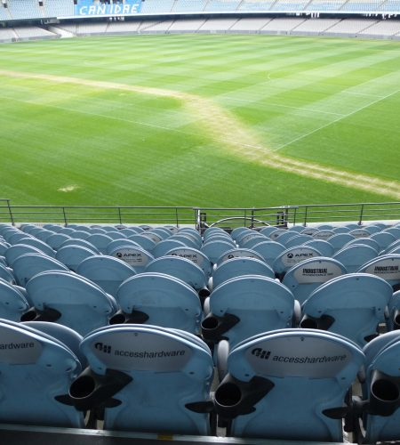 Empty seating at a sports stadium viewed from behind looking down towards the green field below